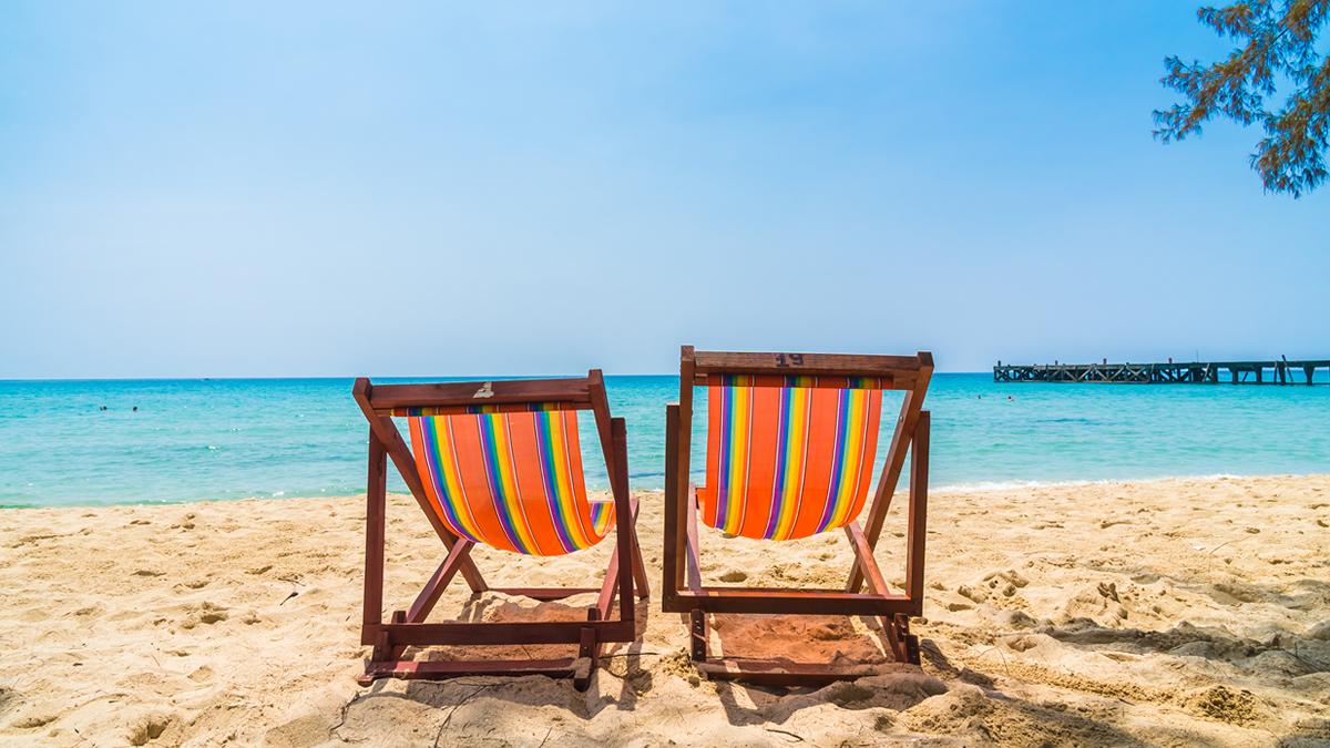 Colourful deck chairs on sandy beach