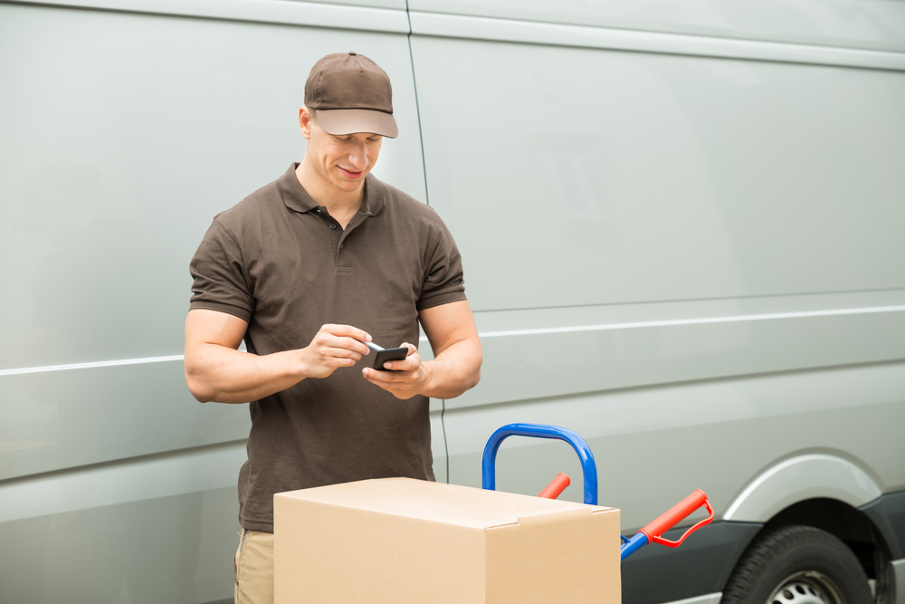 Delivery man using mobile device