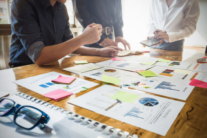 Planning around a conference table with post-it notes, graphs and more