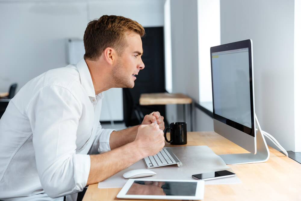 Businessman in shirt looking at white screen on mac
