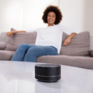Voice assistant in smart device on coffee table with user sat on sofa