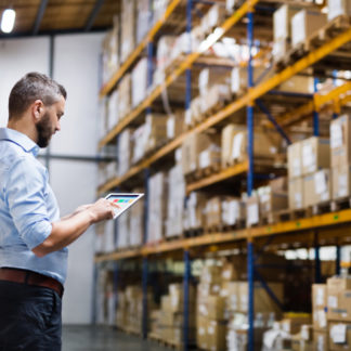 Man in warehouse with tablet, lots of products