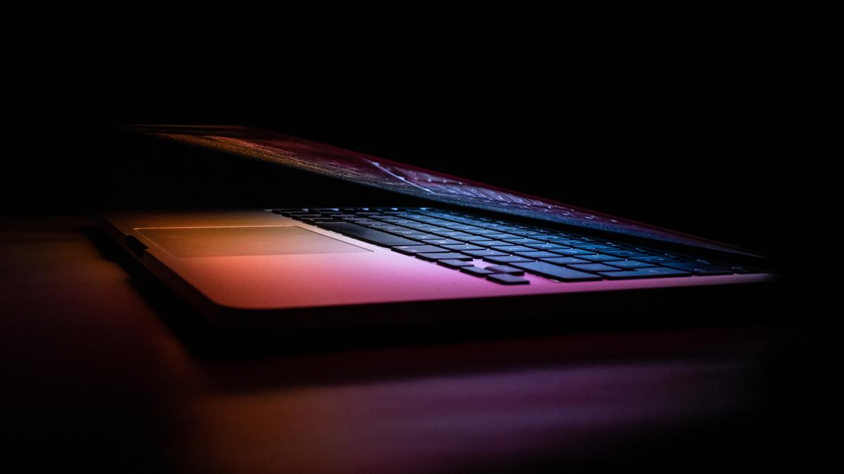 half open laptop in dark - sunset colours