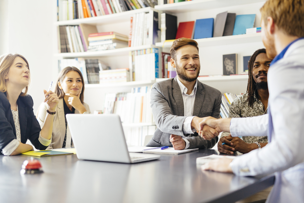 Business client handshake at meeting table
