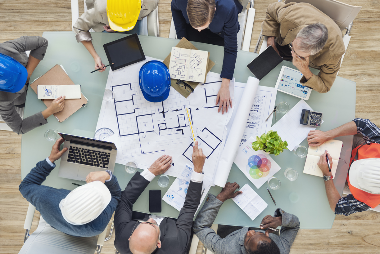 Architect meeting roudn table with hard hats and plans