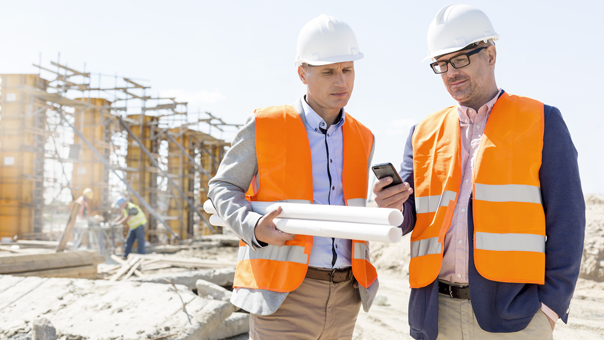 Construction workers looking at plans and a mobile phone