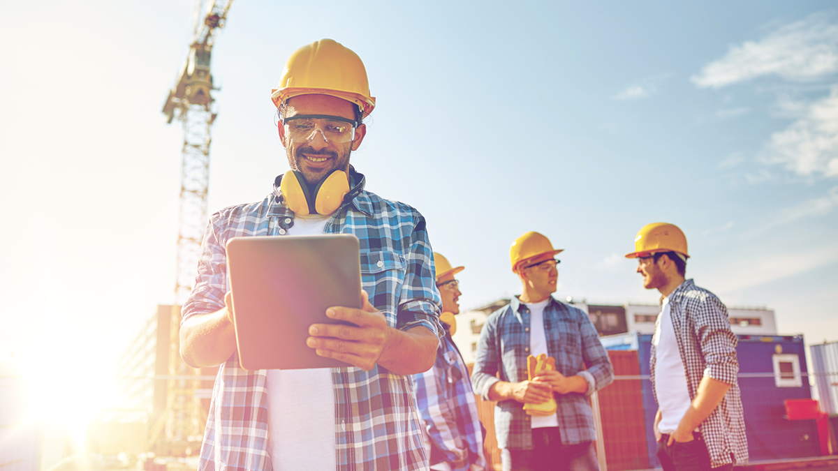 Man in a hard hat with ear defenders off using his tablet device, crane and other builders in the background