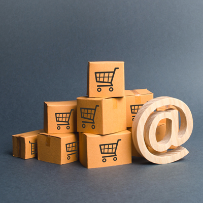 "Cart symbol on cardboard boxes behind wooden email symbol ""@"""